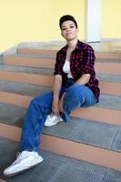 Beautiful african american woman with short hair, outside sitting on the stairs photo