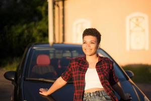 Beautiful African American woman with short hair near the car, lifestyle photo