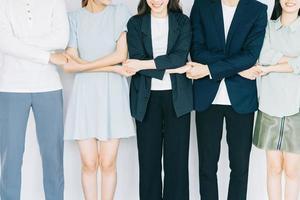 jóvenes empresarios asiáticos se toman de la mano para mostrar solidaridad foto