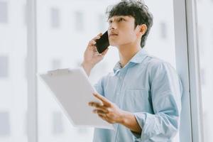 El empresario asiático está llamando para discutir sobre el trabajo junto a la ventana. foto