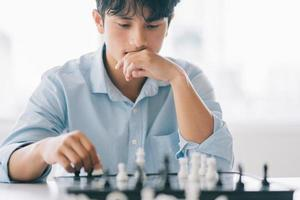 Asian businessman is thinking about his next move on the chess board photo