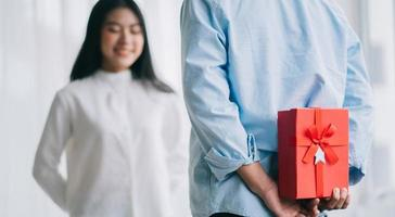 Asian girl feels happy and surprised to receive gifts from her boyfriend on valentine's day photo