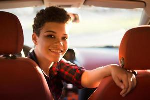 Happy and beautiful african american woman with short hair in a car, lifestyle photo
