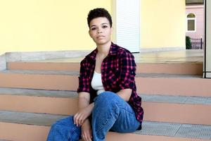 Beautiful african american woman with short hair, outside sitting on the stairs, lifestyle photo