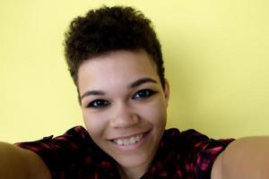 Beautiful and happy African American woman with short hair on a yellow background, takes a selfie, close-up portrait photo