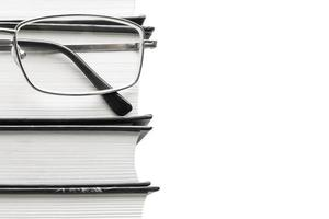 Glasses and thick books on a white background photo