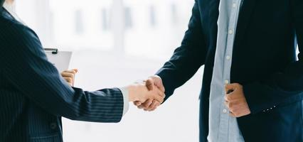 Two young Asian businessmen shake hands after signing a contract photo