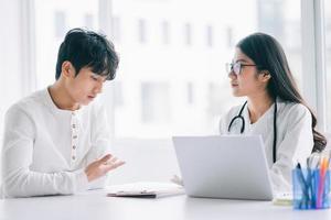 La doctora asiática está comprobando la salud del paciente. foto