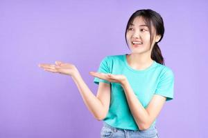 Young Asian girl in cyan shirt on purple background photo