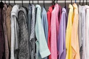 Different color bathrobes on the hanger in the shower room photo