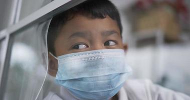 garçon portant un masque assis à côté de la fenêtre video