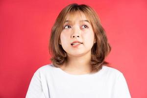 Joven asiática con gestos y expresiones alegres en el fondo foto