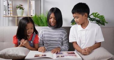 Three kids reading a book. video
