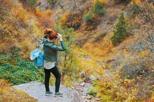 Female hiker walking in mountains forest. photo