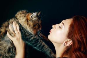 chica pelirroja tiene gato mullido sobre fondo negro. foto