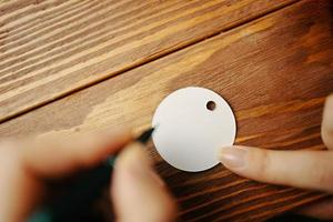 manos de mujer con lápiz y etiqueta en blanco de regalo. foto