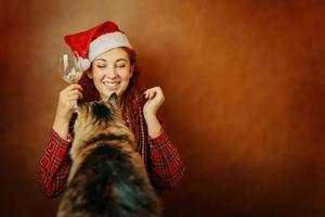 mujer pelirroja con sombrero de santa claus y gato esponjoso. foto