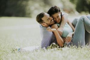 Afectuosa pareja joven sentada en la hierba verde foto