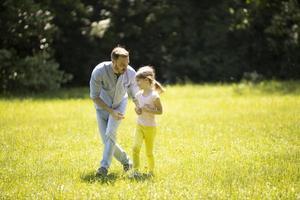 padre persiguiendo a su pequeña hija mientras jugaba en el parque foto