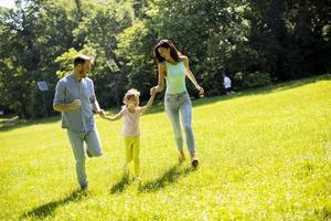 Familia joven feliz con linda hijita corriendo en el parque en un día soleado foto