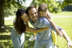 Familia joven feliz con linda hijita divirtiéndose en el parque en un día soleado foto