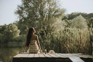 Relaxing young woman on wooden pier at the lake photo