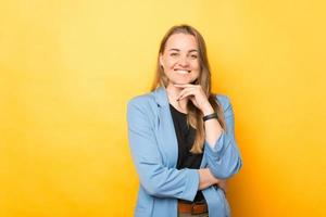 Portrait of smiling young cheerful woman in casual looking at camera over yellow background photo