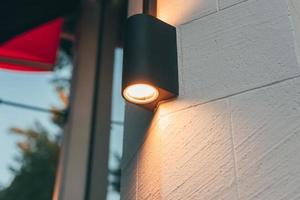 una foto de una farola en un edificio moderno que ilumina las paredes exteriores de la construcción por la noche