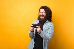 Foto de alegre joven barbudo jugando juegos en el teléfono inteligente sobre fondo amarillo