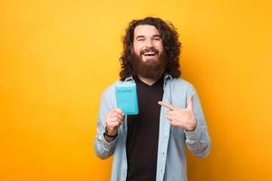 Cheerful amazed bearded hipster man pointing at passport over yellow background, lets go travel photo