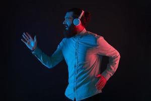 Foto de hipster hombre con barba usando audífonos inalámbricos y corriendo sobre un fondo oscuro con luz de neón