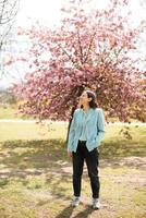 una foto de una mujer joven sentada en medio de la naturaleza y sonriendo está disfrutando