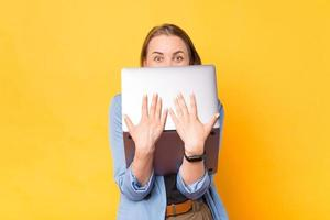 Photo of amazed business woman covering face with laptop and looking at camera over yellow background