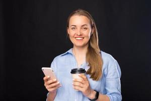 Close up portrait of business woman smiling and holding smartphone and paper coffee cup photo