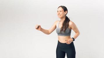 Foto de mujer joven deporte corriendo y escuchando música sobre fondo blanco.