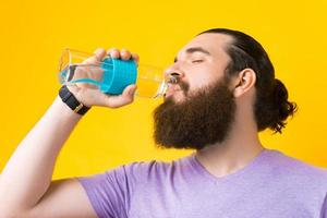 Close up photo of bearded man drinking water from bottle glass over yellow background