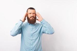 Foto de hombre barbudo con camisa azul con migraña, trabajo de oficina duro