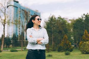 Portrait of young woman in casual standing outdoor in city and looking away photo