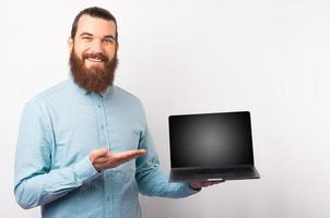 Handsome man in casual blue shirt showing blank screen on laptop and smiling over white wall photo