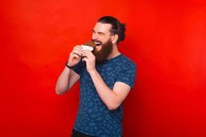 Foto de hipster barbudo hombre comiendo barra de chocolate sobre fondo rojo.