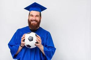 Cheerful smiling bearded man in bachelor holding soccer ball photo