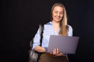 retrato, de, sonriente, joven, mujer casual, usar la computadora portátil, y, llevando, mochila foto