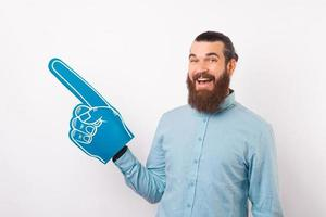 Hey look at this, handsome cheerful bearded man in casual pointing away with fan glove photo