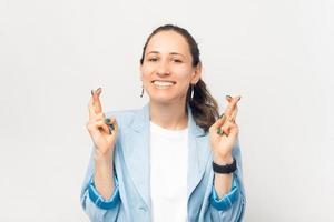 Portrait of young business woman crossing fingers and wishing for the best photo