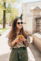 una bonita foto de una joven feliz caminando cerca de un edificio y charlando con alguien en su teléfono