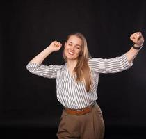 Photo of young business woman celebrating victory over dark background