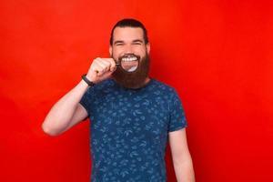 Foto de hombre barbudo alegre mostrando su gran sonrisa a través de una lupa