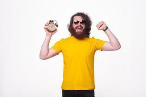 Amazed man with beard and wearing yellow t-shirt holding alarm clock photo