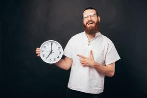 Photo of amazed bearded hipster man pointing at big white clock