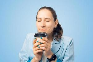 Close up portrait of young woman smelling her morning tasty coffee photo